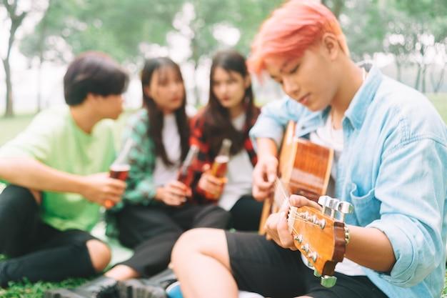 Gruppe glücklicher junger asiaten beim picknick im park picnic