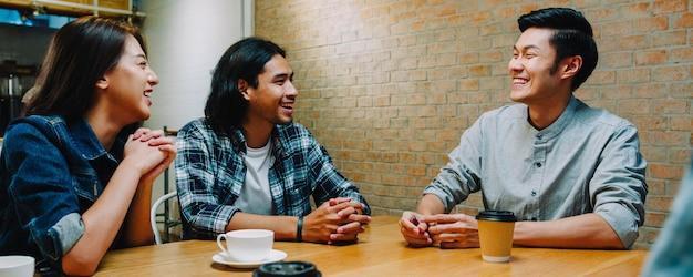 Gruppe glücklicher junger asiatischer freunde, die spaß haben und lachen, während sie zusammen im café-restaurant sitzen.