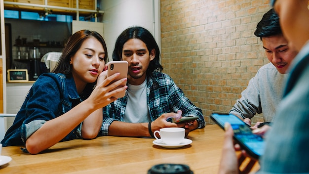 Gruppe glücklicher junger asiatischer freunde, die spaß haben und zusammen smartphone verwenden, während sie zusammen im café-restaurant sitzen