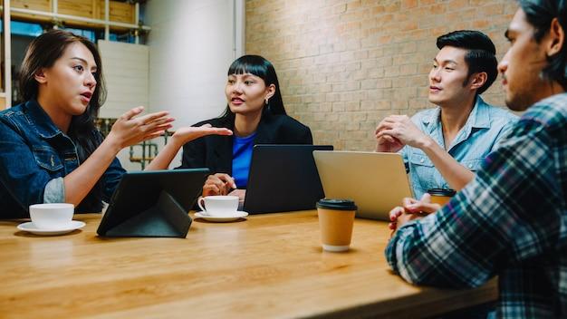 Gruppe glücklicher junger asiatischer geschäftsmitarbeiter, die laptop in ungezwungener teambesprechung verwenden, startprojektdiskussion im caférestaurant