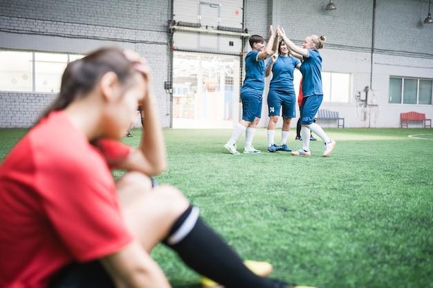 Gruppe glücklicher junger frauen in blauer sportbekleidung, die triumph auf rivalisierende mannschaft nach fußballspiel ausdrücken