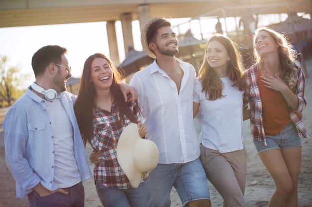 Gruppe glücklicher junger freunde, die lachen und eine tolle zeit am strand haben?