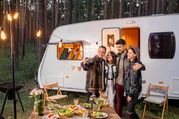 Gruppe glücklicher junger freunde, die selfie mit dem wohnmobil machen