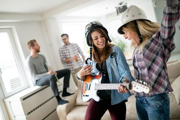 Gruppe glücklicher junger leute, die zusammen spaß haben und in der musikband spielen