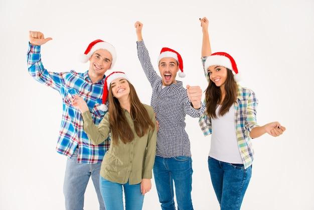 Gruppe glücklicher junger leute in weihnachtsmützen