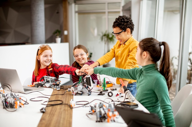 Gruppe glücklicher kinder, die elektrisches spielzeug und roboter im robotikklassenzimmer programmieren