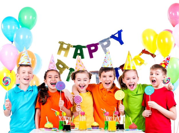 Gruppe glücklicher kinder mit bunten bonbons, die spaß an der geburtstagsfeier haben - lokalisiert auf einem weiß.