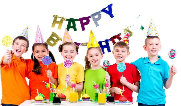 Gruppe glücklicher kinder mit bunten bonbons, die spaß an der geburtstagsfeier haben - lokalisiert auf einem weiß