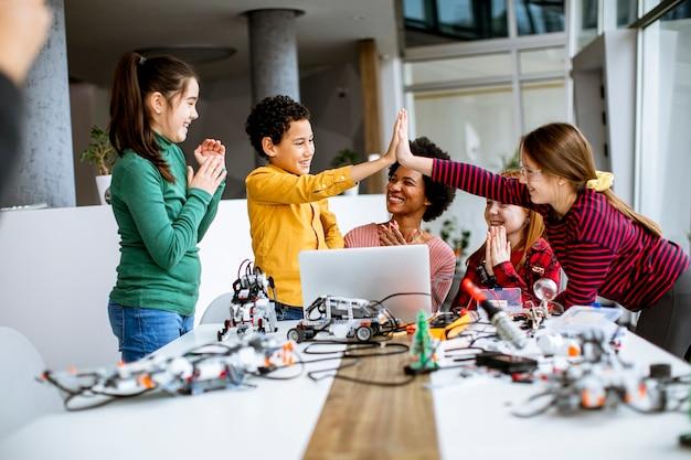 Gruppe glücklicher kinder mit ihrer afroamerikanischen lehrerin für naturwissenschaften