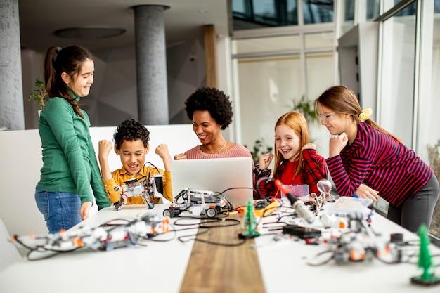 Gruppe glücklicher kinder mit ihrer afroamerikanischen wissenschaftslehrerin mit laptop, der elektrisches spielzeug und roboter am robotikklassenzimmer programmiert