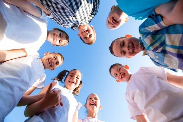 Gruppe glücklicher kinder von jungen und mädchen im parkblick vom boden aus