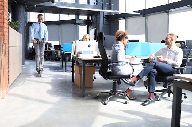 Gruppe glücklicher progressiver geschäftsleute, die gemeinsam im kreativbüro am start arbeiten.