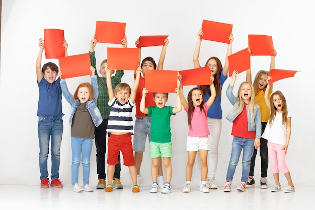 Gruppe glücklicher schreiender kinder mit roten leeren fahnen einzeln im weißen studiohintergrund. bildungs- und werbekonzept. protest- und kinderrechtskonzepte.