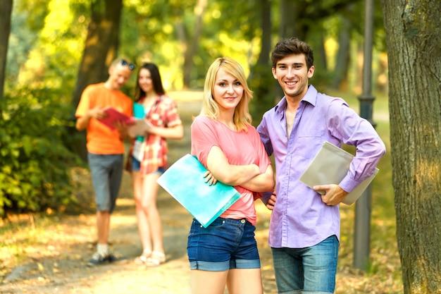 Gruppe glücklicher schüler mit büchern im park an einem sonnigen tag
