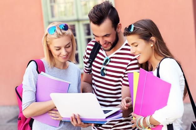 Gruppe glücklicher studenten, die im freien studieren