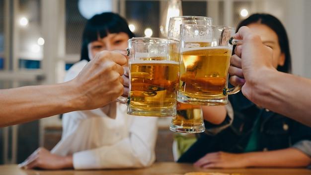 Gruppe glücklicher touristischer junger asiatischer freunde, die alkohol oder craft-bier trinken und eine hangout-party im nachtclub in der khao san road veranstalten.