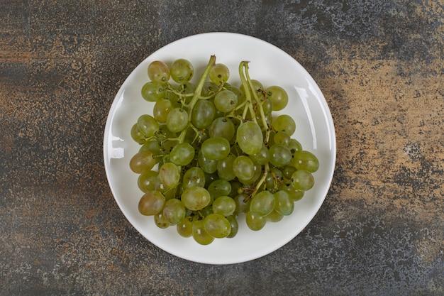 Gruppe grüner trauben auf weißem teller.
