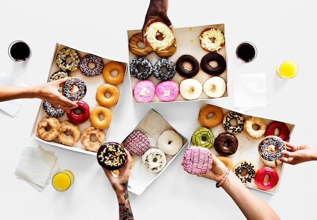 Gruppe hände, die süßen donutnachtisch halten