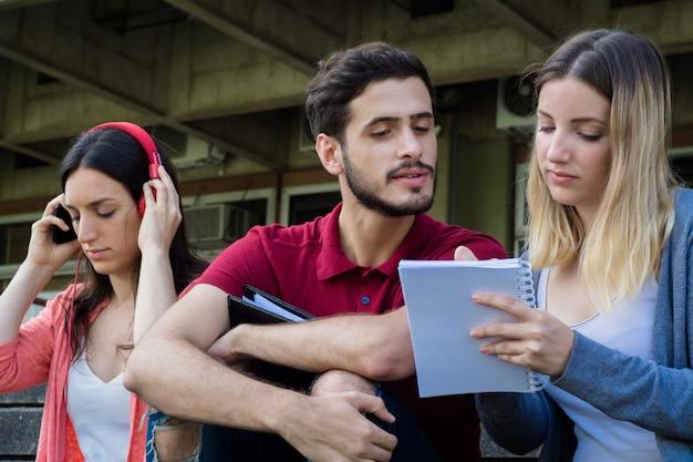 Gruppe hochschulstudenten, die zusammen draußen studieren