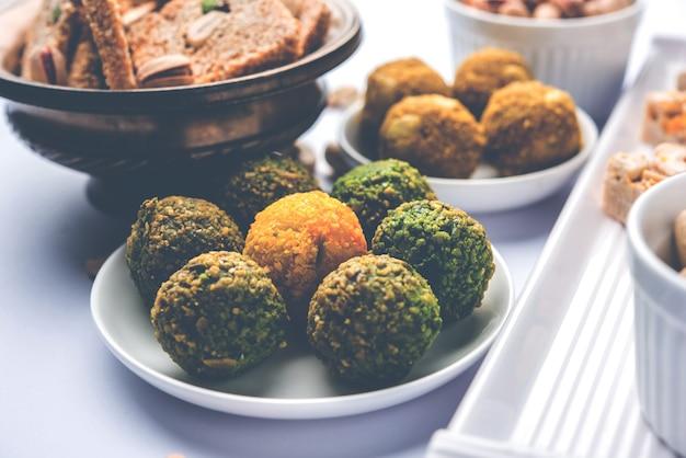 Gruppe indischer festsüßigkeiten wie trockenfrüchte laddu, kaju katli, burfi, gajak, til papdi, rasmalai, gulab jamun. selektiver fokus