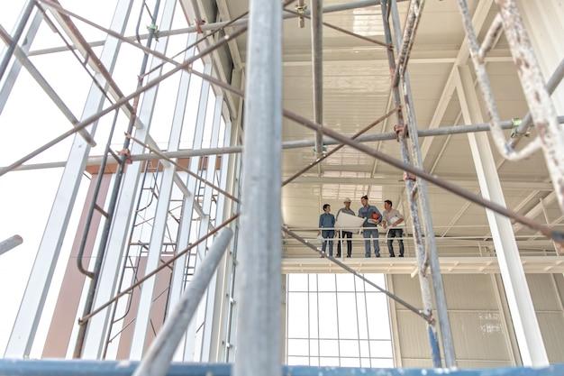 Gruppe ingenieure, mann und frau, zusammenarbeitend in der baustelle