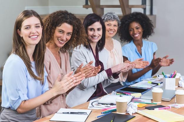 Gruppe innenarchitekten, die im büro applaudieren