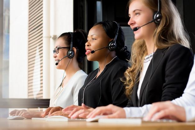 Gruppe internationale geschäftsfrauen, die in call-center arbeiten
