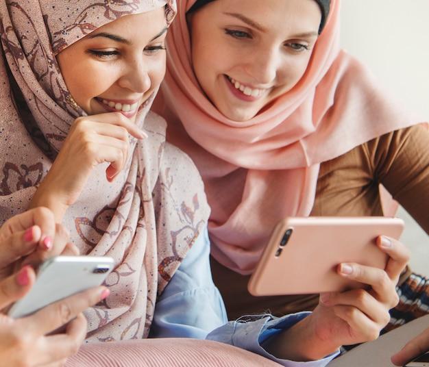 Gruppe islamische frauen, die zusammen am telefon sprechen und aufpassen
