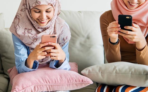 Gruppe islamische mädchen, die auf der couch sitzen und intelligente telefone verwenden