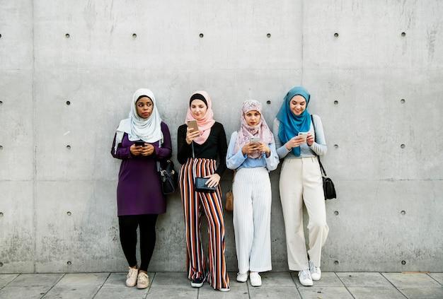Gruppe islamische mädchen, die intelligentes telefon verwenden