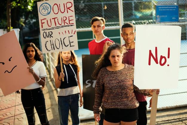 Gruppe jugendlichen, welche die demonstration hält plakate antikriegsgerechtigkeitsfriedenskonzept protestieren