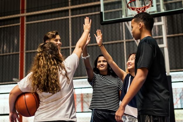 Gruppe jugendlichfreunde auf einem basketballplatz, der sich hohe fünf gibt