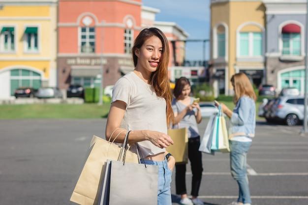 Gruppe junge asiatin beim einkaufen in einem markt im freien mit einkaufstüten in ihren händen