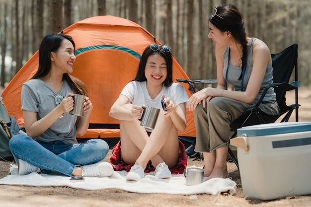 Gruppe junge asiatische freunde, die zusammen im wald kampieren oder picknicken