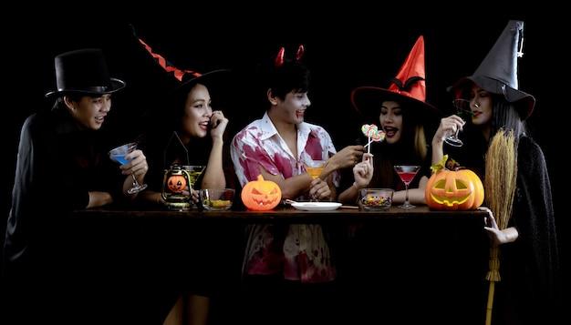 Gruppe junge asiatische im kostüm feiern halloween-party auf schwarzer wand mit konzept für halloween-modefestival .. kostümgeist, böse der gruppe teen thai.