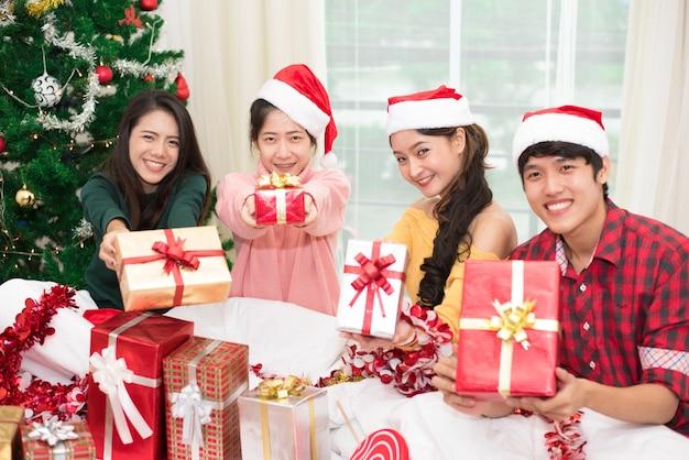 Gruppe junge asiatische leute, die geschenkbox zu ihnen mit weihnachtsbaumhintergrund halten und geben