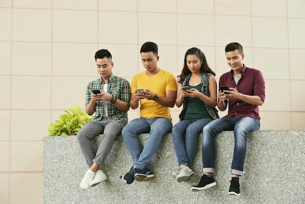Gruppe junge asiatische leute, die in der straße sitzen und smartphones verwenden