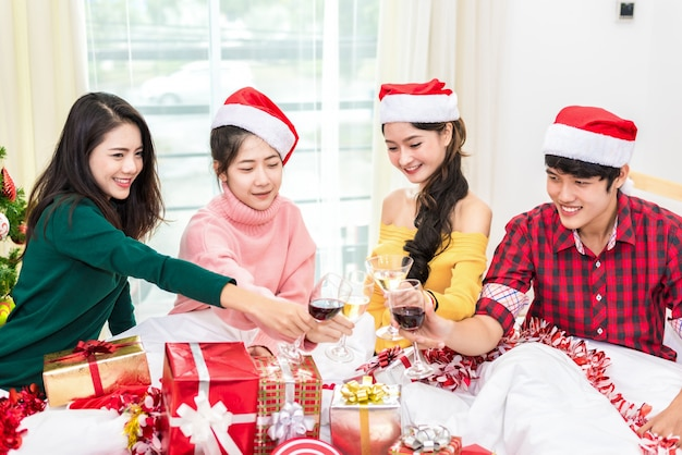 Gruppe junge asiatische leute, die partei des neuen jahres im haus mit trinkenden gläsern des weins feiern