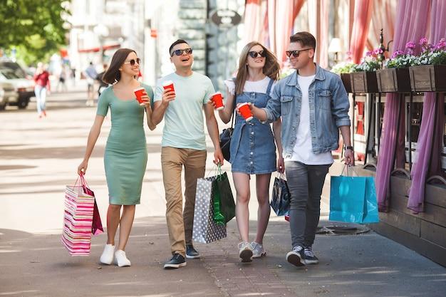 Gruppe junge attraktive leute, die das einkaufen bilden. freunde, die draußen einkaufstaschen und das lächeln halten. fröhliche freunde zusammen.