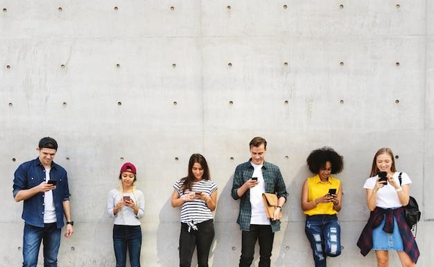 Gruppe junge erwachsene draußen unter verwendung der smartphones zusammen und kühlend