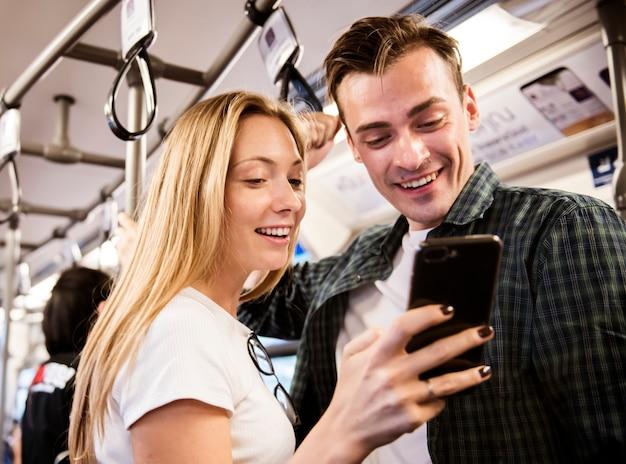 Gruppe junge erwachsene freunde, die smartphones in der u-bahn verwenden