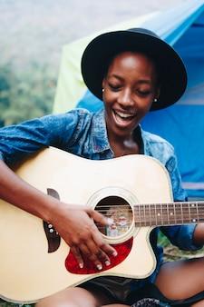 Gruppe junge erwachsene freunde im campingplatz gitarre spielend und zusammen draußen entspannend singend