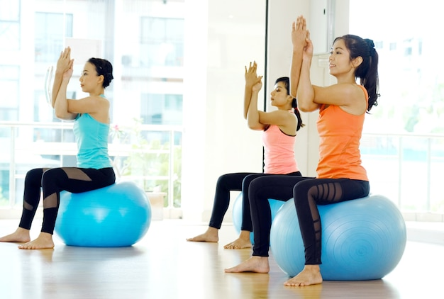 Gruppe junge frauen, die körper auf yogakugeln in der studioübungsklasse ausdehnen