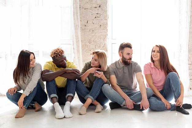 Gruppe junge freunde, die auf fußboden sitzen