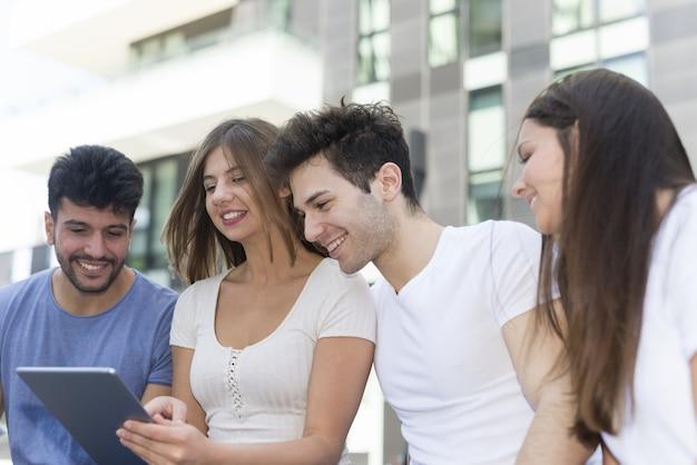 Gruppe junge freunde, die zusammen eine tablette verwenden