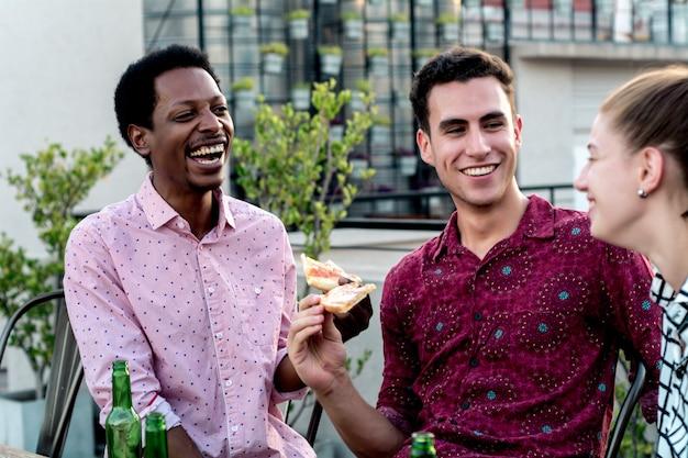 Gruppe junge freunde mit pizza und flaschen getränk