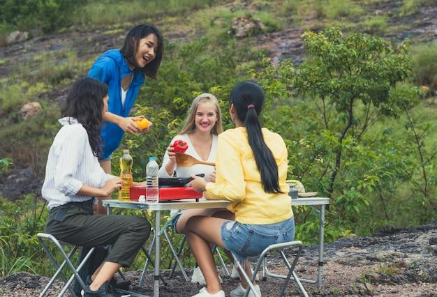 Gruppe junge freundinnen der verschiedenartigkeit genießen, für abendessen beim kampieren im wald zusammen zu kochen