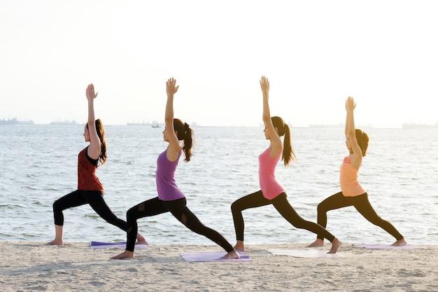 Gruppe junge gesunde frauen, die yoga auf dem strand, gesunde lebensstile, wellness, wohl tun