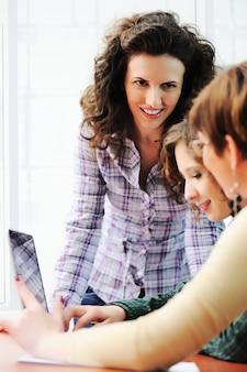 Gruppe junge glückliche leute, die den laptop arbeitet an ihm untersuchen