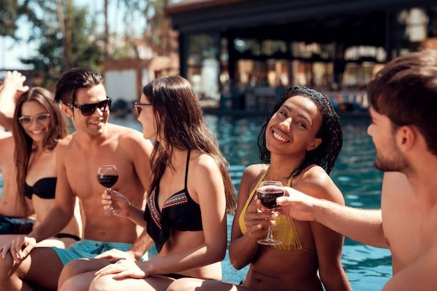 Gruppe junge glückliche leute, die zusammen am poolside sitzen